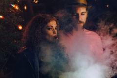 Foto auf dem ein junger Mann und eine junge Frau zu sehen sind. Das Foto wurde in der Nacht aufgenommen. Die Dame nimmt einen Zug von einem Verdampfer, der enorm voluminöse Rauchwolken produziert.