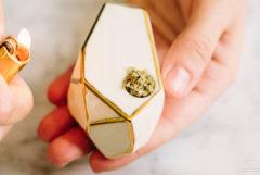 Een hand met een lichter in een witte en gouden cannabispijp