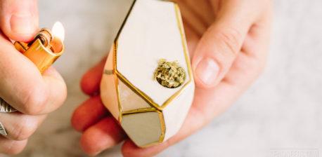 Eine Hand, die ein Feuerzeug zu einer weißen und goldenen Cannabis-Pfeife hält