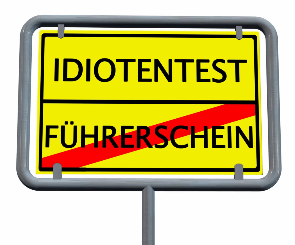Fotografía de una señal de tráfico amarilla que muestra el texto «Test idiota» en la parte superior y «Permiso de conducir» en la inferior. Las palabras «Permiso de conducir» están tachadas con una línea roja.