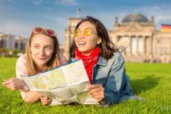 Foto van twee jonge vrouwelijke toeristen die op een grasveld voor het Rijksdaggebouw in Berlijn liggen. Ze staren vrolijk in de verte en hebben een kaart van de stad in hun handen.