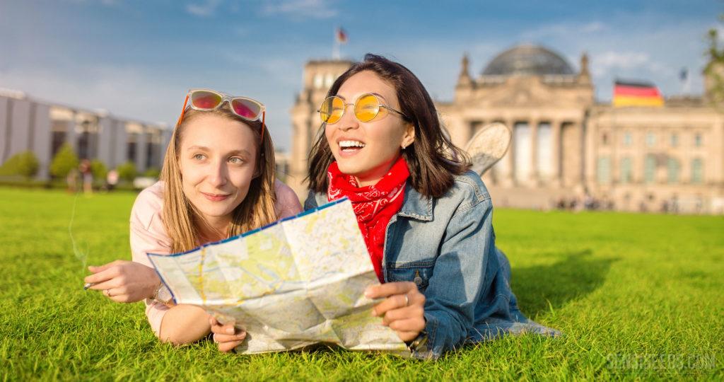 Zwei junge Mädchen, die auf dem Gras liegen und eine Karte anhalten. Man hält ein Gelenk