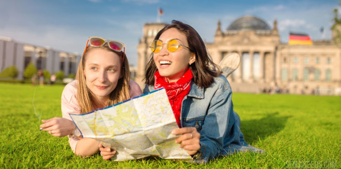 Photo of two young female tourists lying on a large lawn in front of the Reichstag parliament building in Berlin. They are gazing happily into the distance and holding a map of the city in their hands.