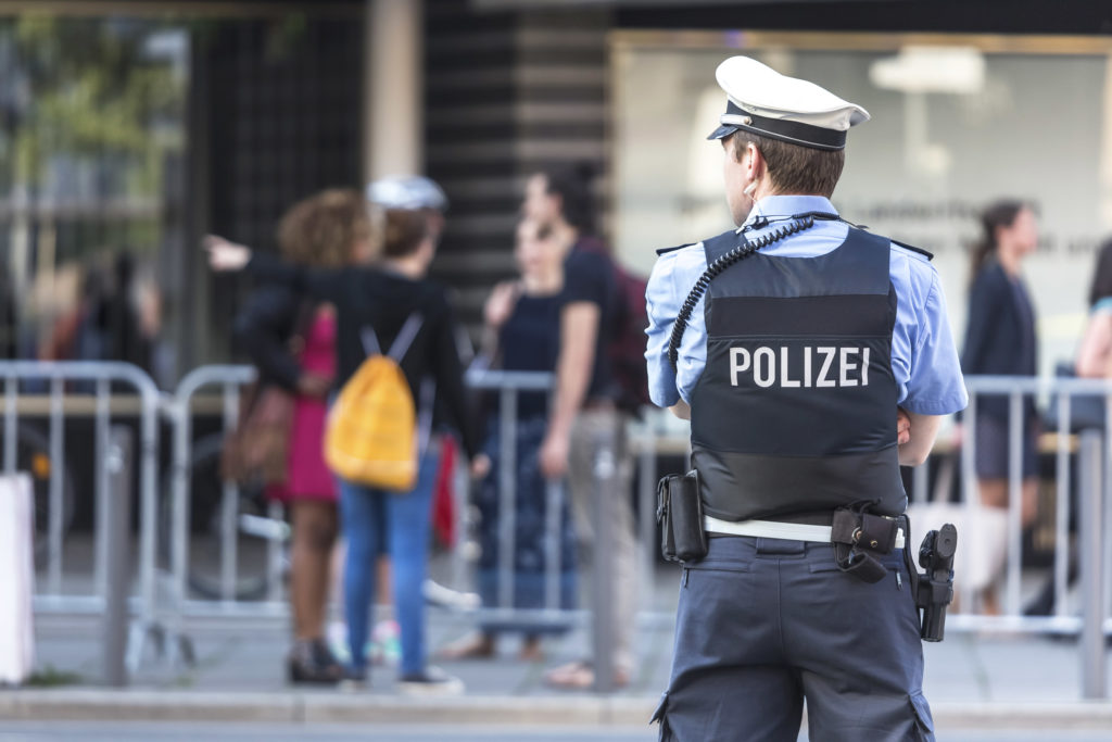 Photo of a German policeman taken from behind. He is looking slightly to one side. In front of him is a group of people who are out of focus.