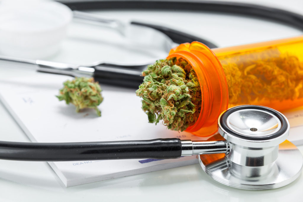 Close-up of an orange container containing medicinal cannabis buds next to a stethoscope
