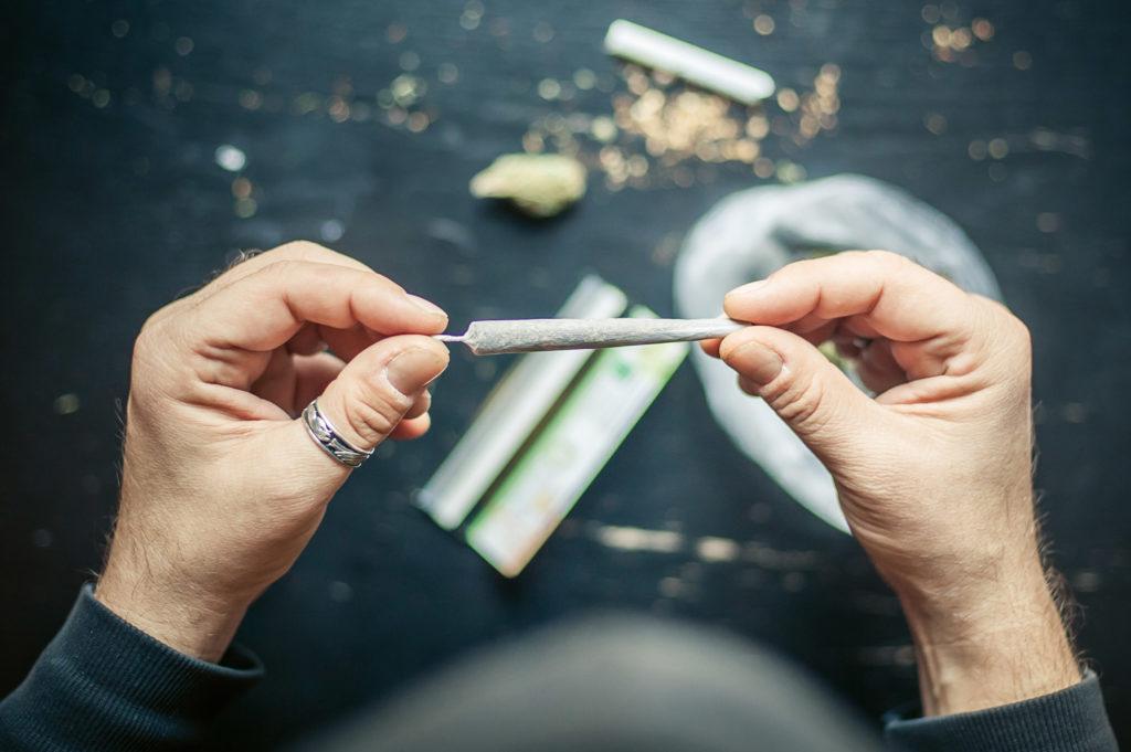 Nahaufnahme von zwei Händen, die einen fertiggedrehten Joint festhalten. Im Hintergrund befinden sich Rauchparaphernalien.