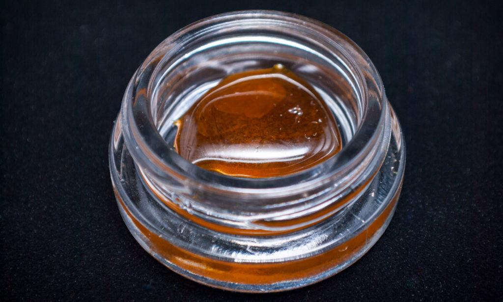 Nahaufnahme eines gläsernen Behälters, der Cannabisöl enthält.