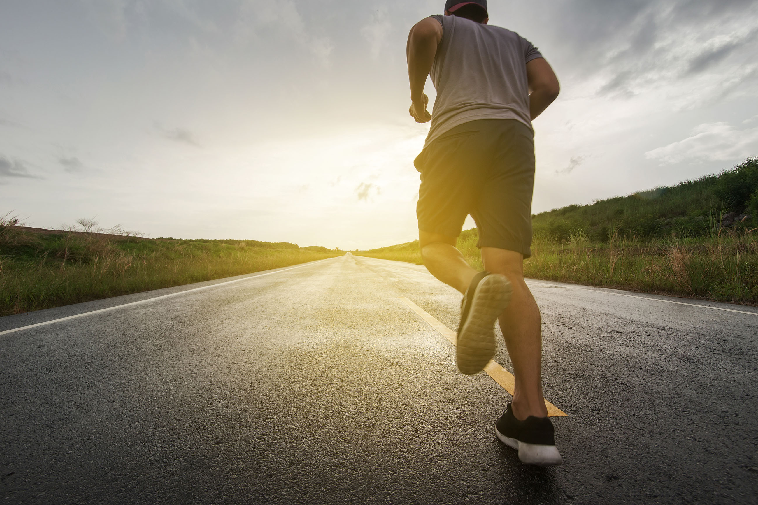A photograph of a man running along an empty road towards the sunset.
