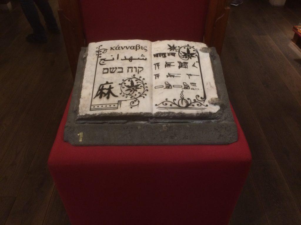 Un antiguo texto hindú. Está en exhibición en un soporte rojo.