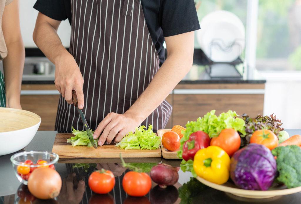 Eine Person, die eine Schürze trägt, hackt Salat und von Gemüse umgeben