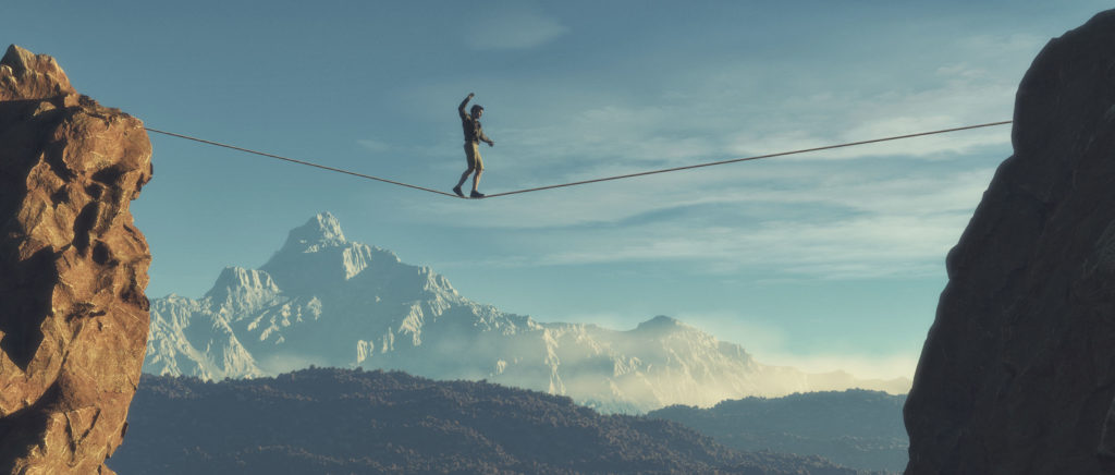 A person crossing a tightrope between two rocks with mountains in the background