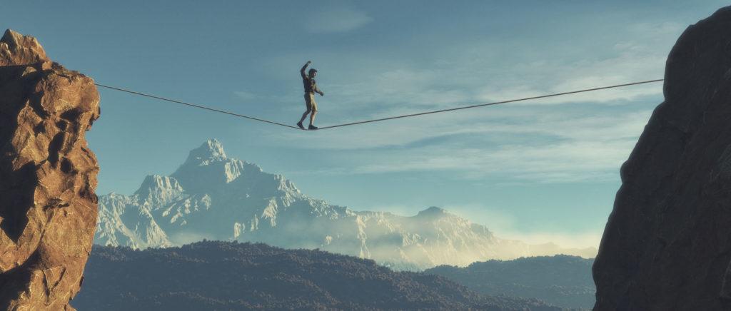 Een persoon die een koord oversteekt tussen twee rotsen met bergen op de achtergrond