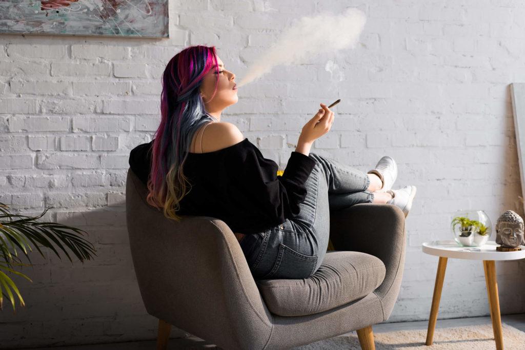Eine Frau mit rosa und blauen Haaren, die auf einem Stuhl räumt und ein Gelenk rauchen