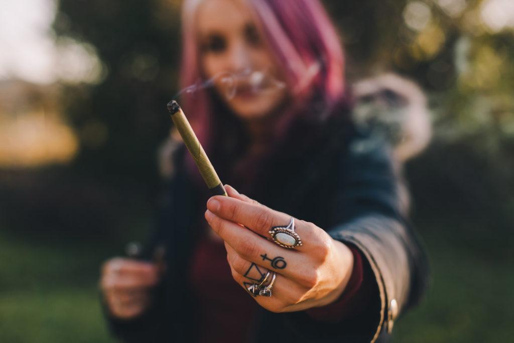 Mujer con pelo de color rosa, alcanzando su mano con anillos y tatuajes, sosteniendo una articulación