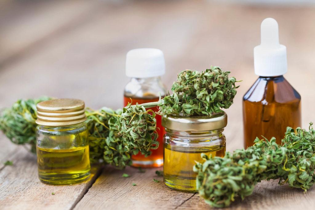 Vier Gläser Gläser von CBD-Öl- und Cannabis-Knospen