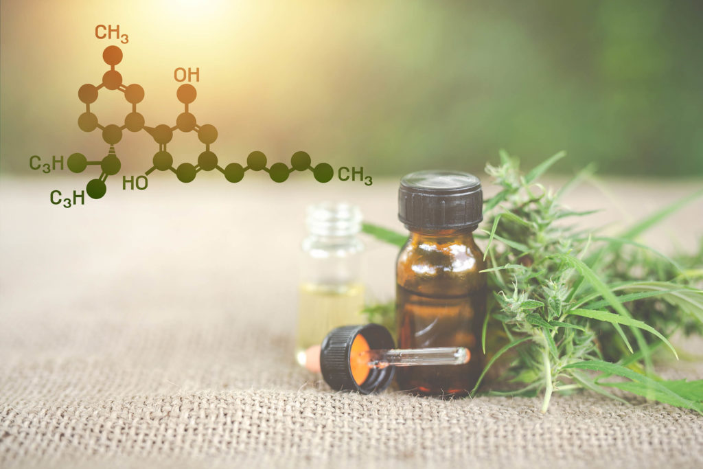 The chemical formula of CBD, two CBD oil bottles and a cannabis plant
