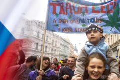 Le drapeau tchèque et un jeune garçon sur les épaules de sa mère à une protestation