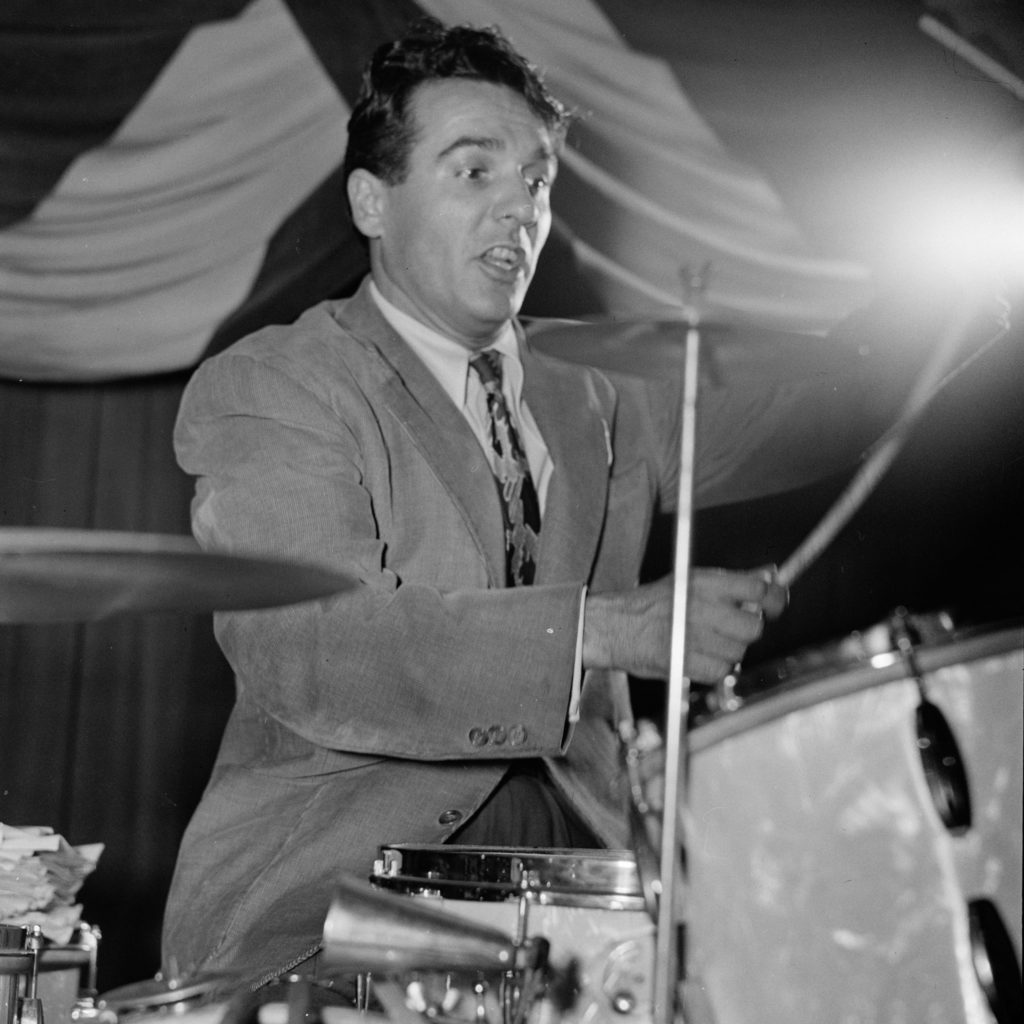 A man wearing a suit and playing the drums