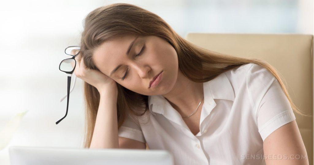 Eine Frau mit dem Schließen der Augen, die ihren Kopf an ihrer Hand stillsteht
