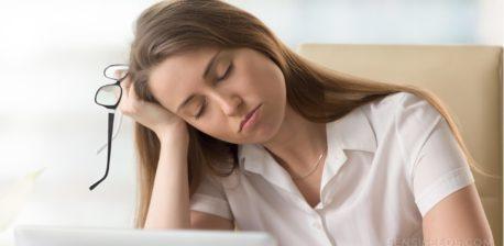 Een vrouw met haar ogen dicht rusten haar hoofd op haar hand