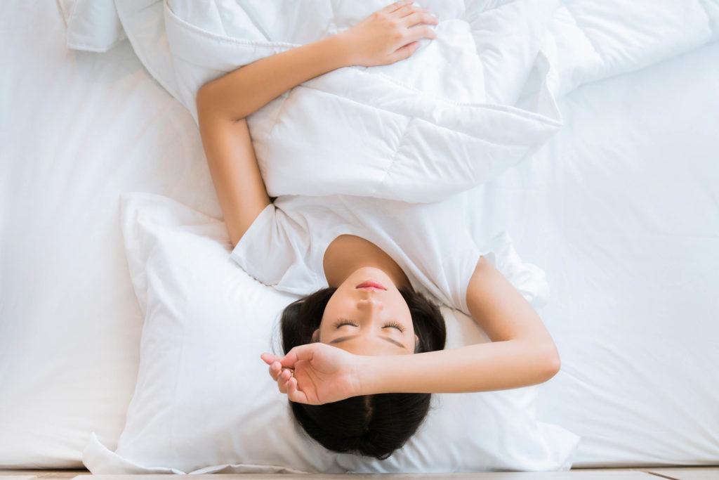 Eine Frau, die im Bett mit ihrem Arm liegt, der über ihre Stirn ruht