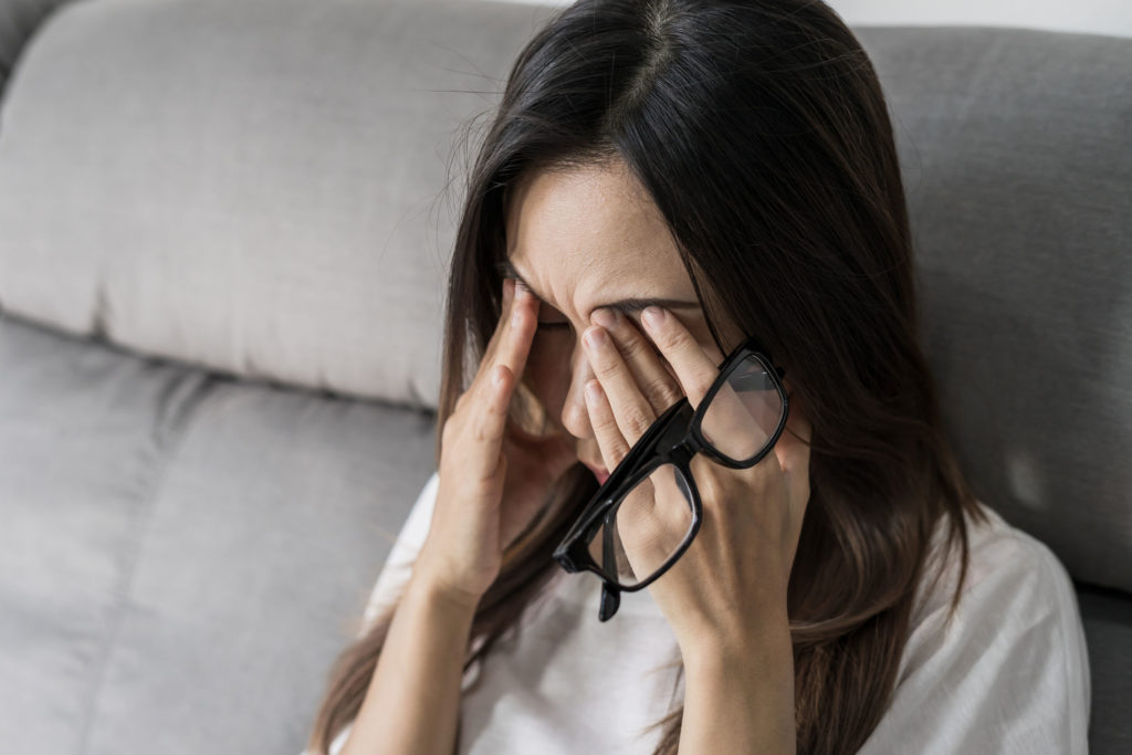 A women with long brown hair pressing her browbone in pain and holding her glasses