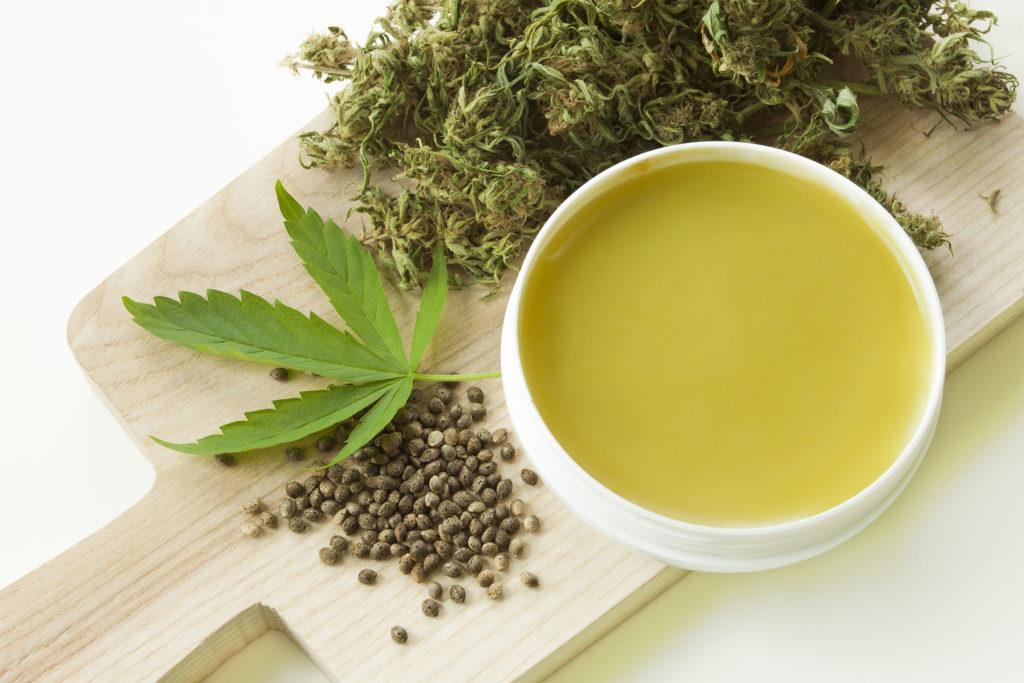 Tres formas diferentes de cannabis en un tablero de madera y ungüento en una olla blanca.