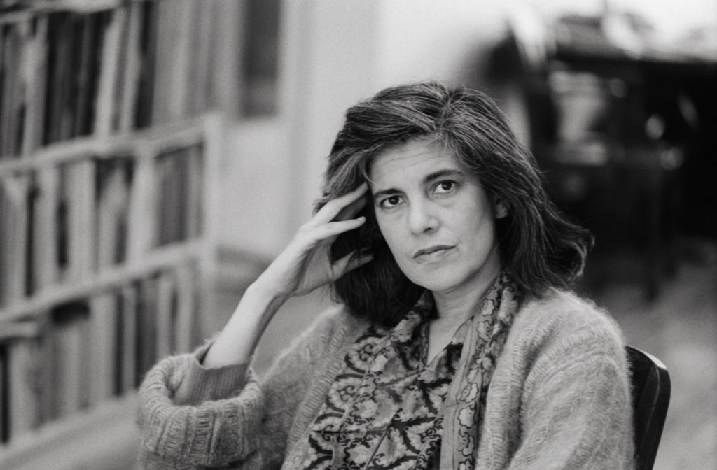 Susan Sontag sat on a chair and resting her head on her hand
