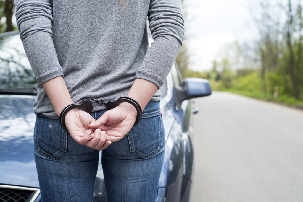 A woman stood in front of a car with her hands handcuffed behind her back