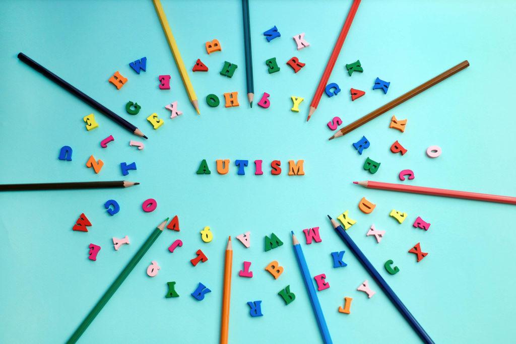 """Verschiedene farbige Bleistifte und Buchstaben, die in einem Kreis um das Wort """"Autismus"""" angeordnet sind"""