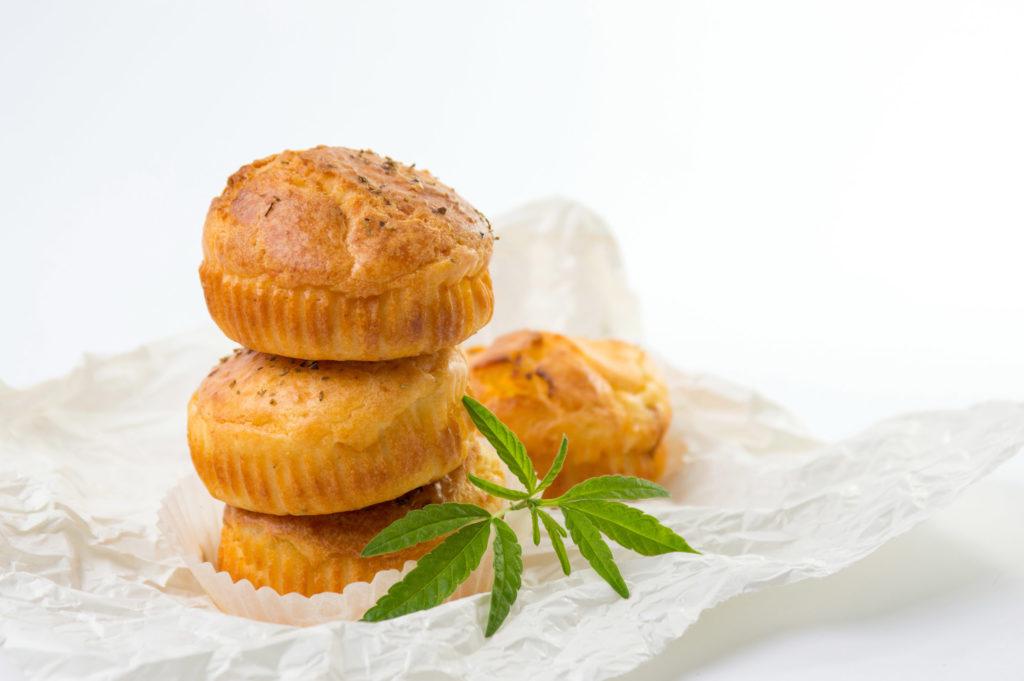 Cuatro pasteles de espacio marrón claro en una envoltura blanca con una hoja de cannabis a su lado.
