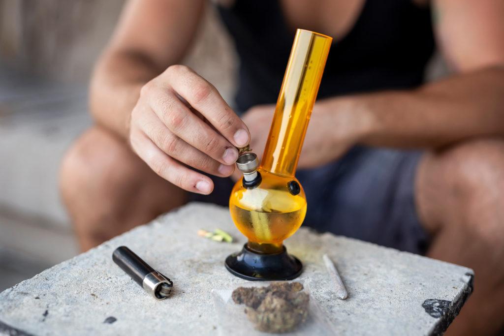 Eine Person, die Cannabis in eine gelbe Bong setzt