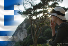 The Greek flag and a woman smoking a joint at the top of a mountain