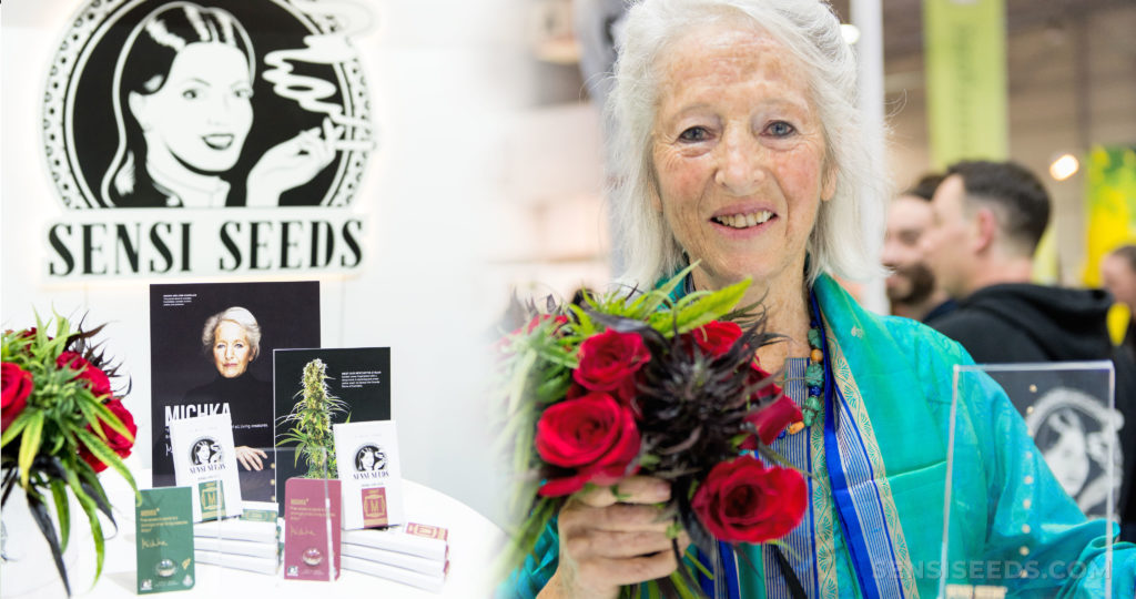 Michka Seeliger-Chatelain holding a bunch of roses next to a Sensi Seeds stand