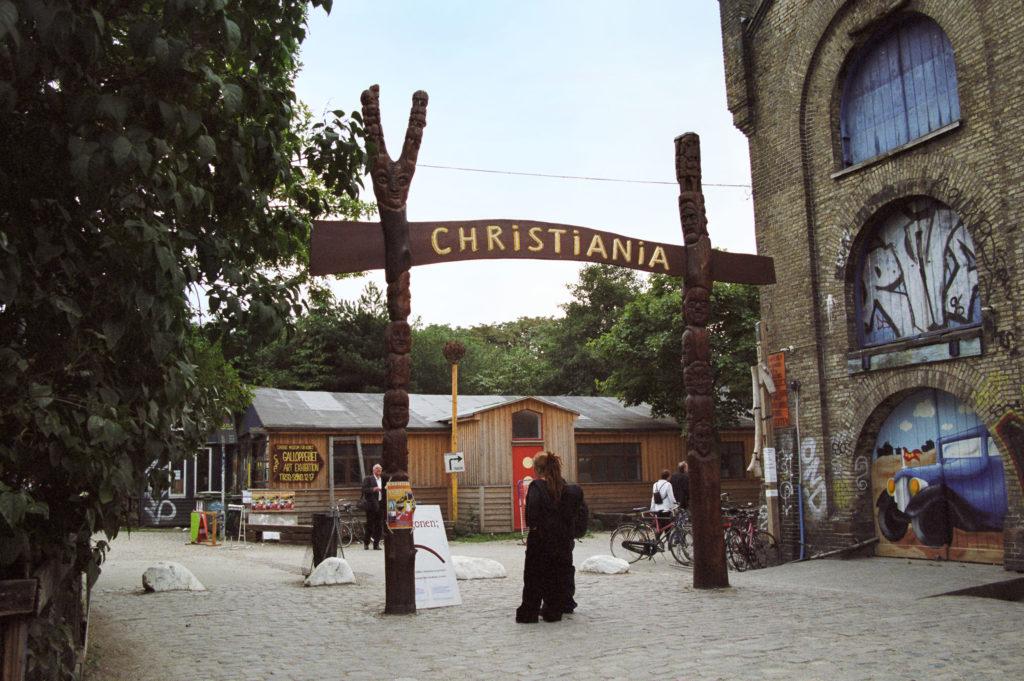 Totem-polen houden een teken 'Christiania' bij aan de ingang van een stad