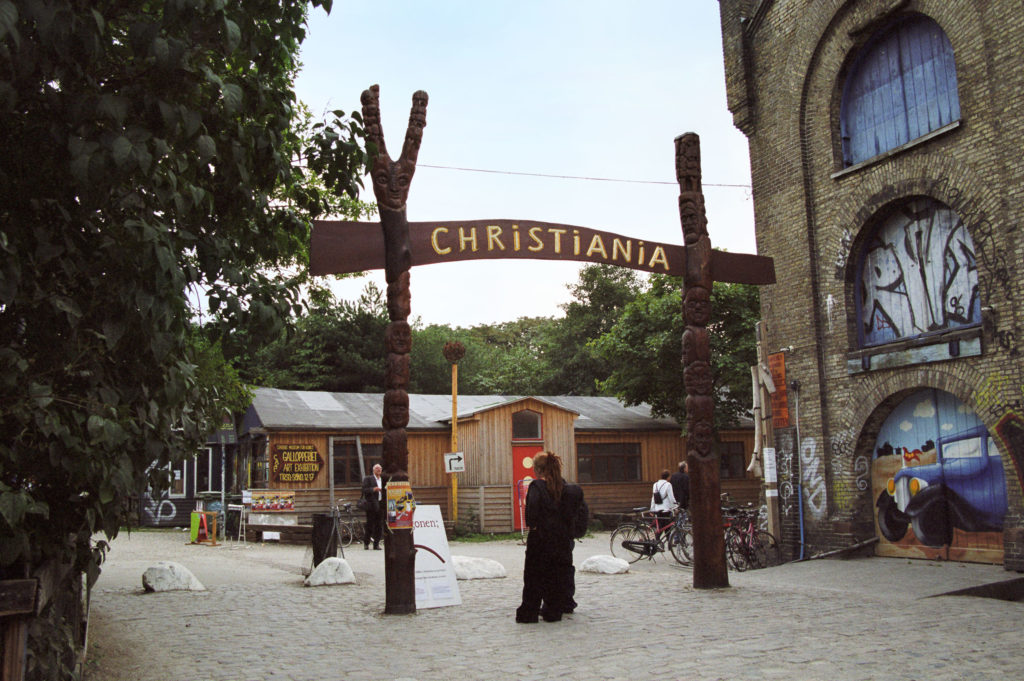 Totem poles holding up a sign 'Christiania' at the entrance to a town