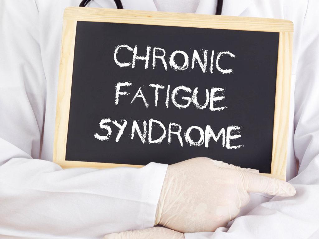 """Ein Doktor, der eine Tafel mit dem """"chronischen Müdigkeitssyndrom"""" hält, das in Kreide geschrieben ist"""