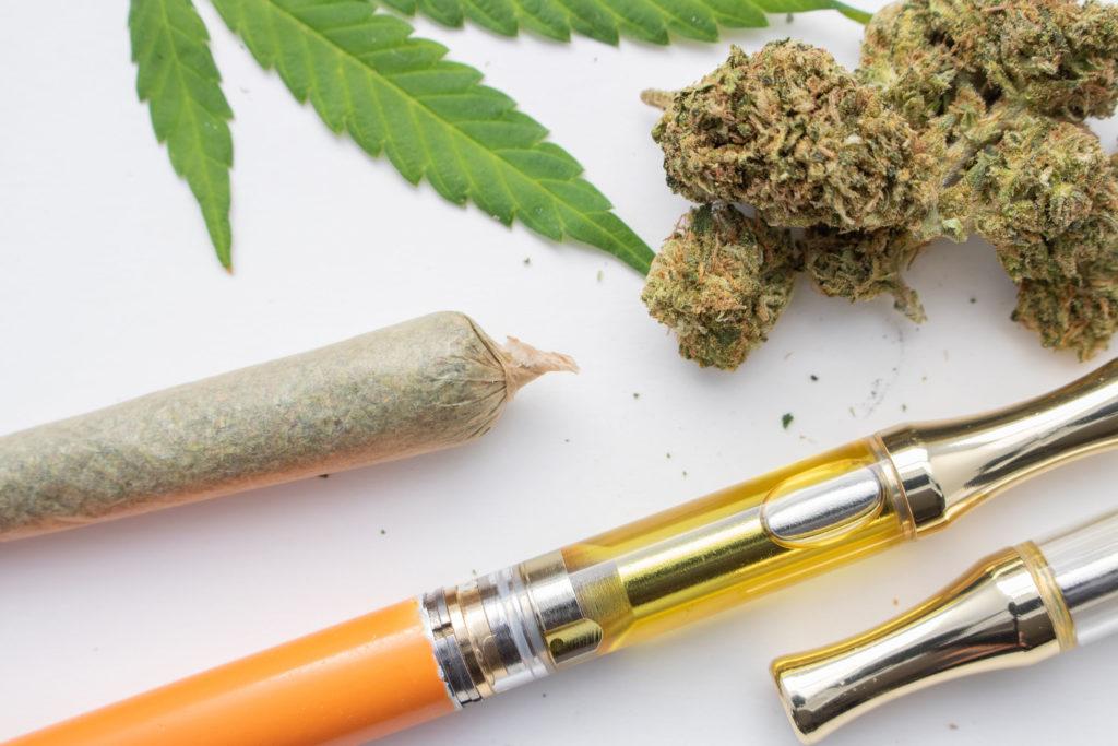 Une articulation roulée, un vaporisateur et des bourgeons de cannabis