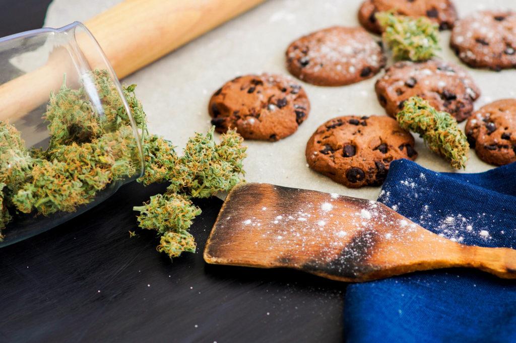 Un rodillo, una cuchara de madera, galletas y un frasco de capullos de cannabis.