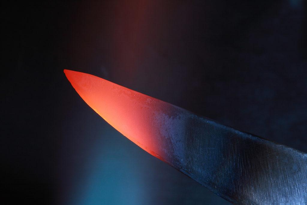 Un cuchillo negro con una punta roja brillante que se ha calentado.
