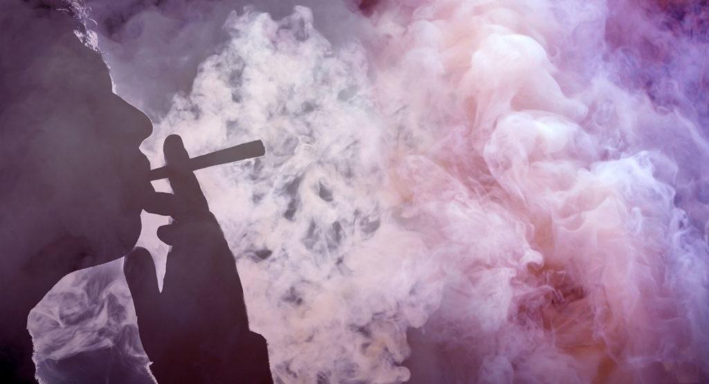 Una silueta de una persona que fumaba una articulación y un montón de humo púrpura.