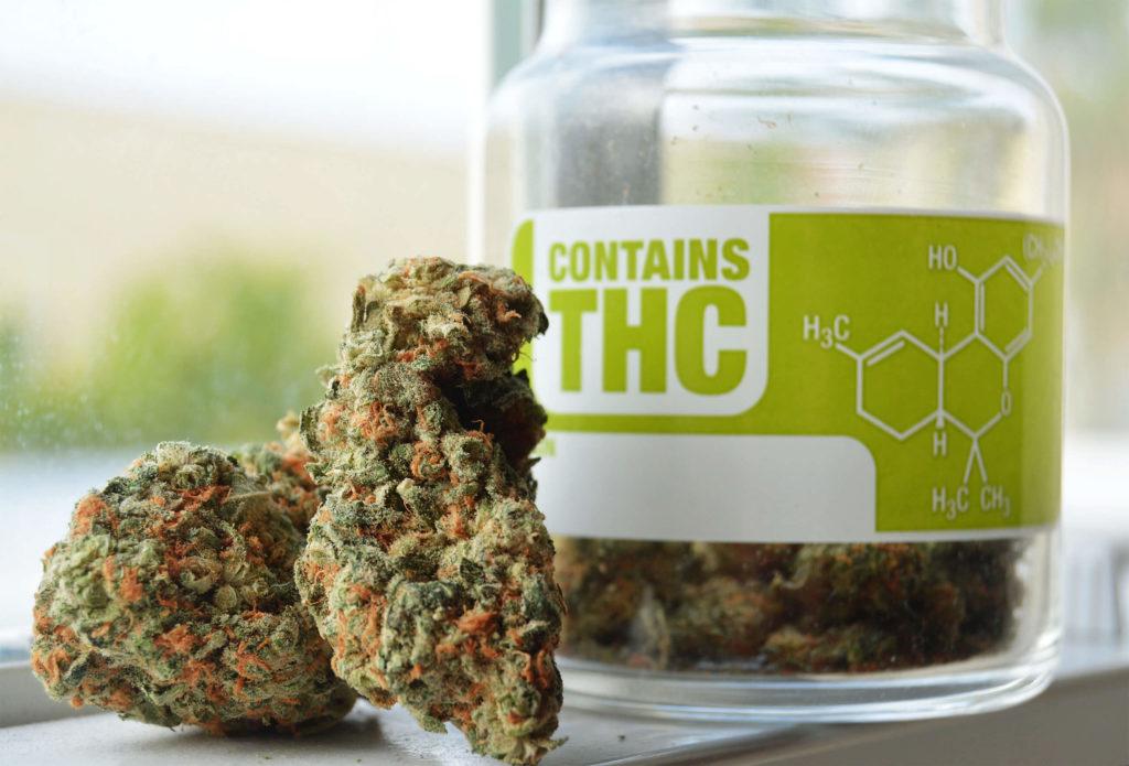 Cannabis-Knospen und ein Glas mit Aufkleber der chemischen Formel von THC