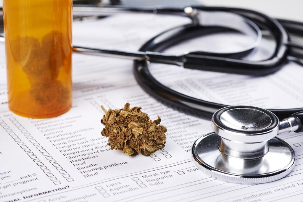 Eine orangefarbene Wanne von Cannabis-Knospen, eine medizinische Form und ein Stethoskop