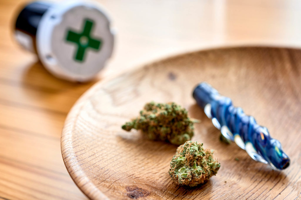 Two buds of cannabis in a wooden bowl, a medical jar and a pipe