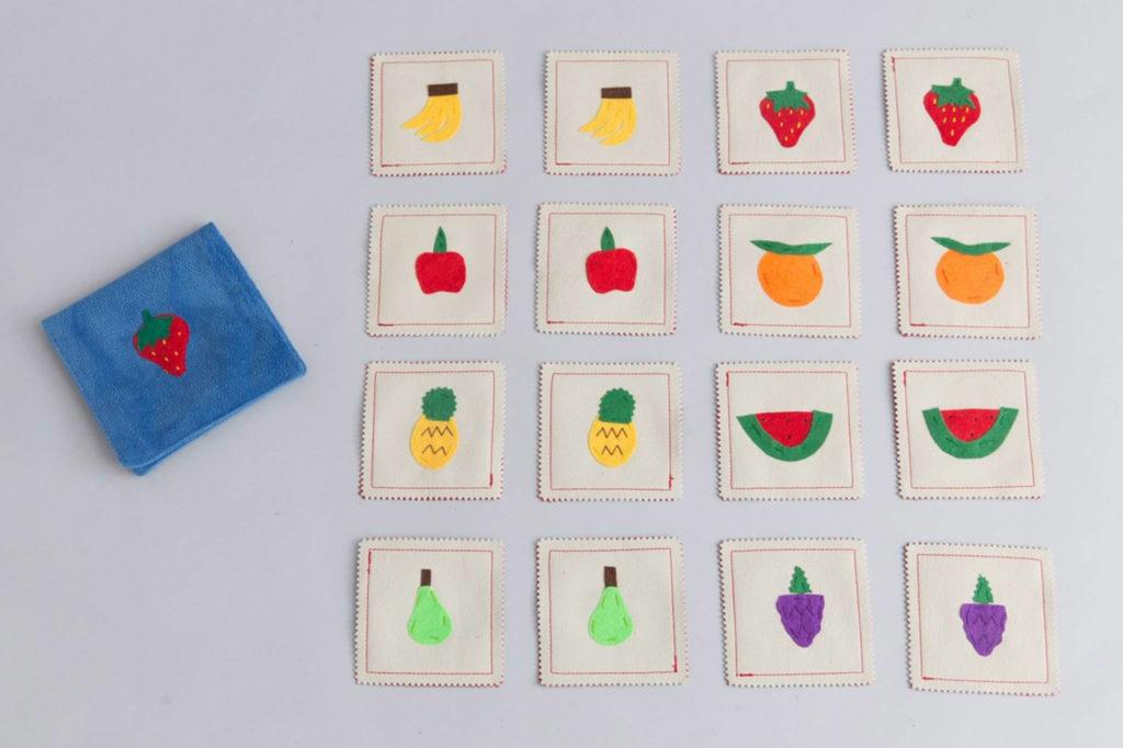 Juego de memoria con frutas pintadas en las cartas sobre superficie gris.