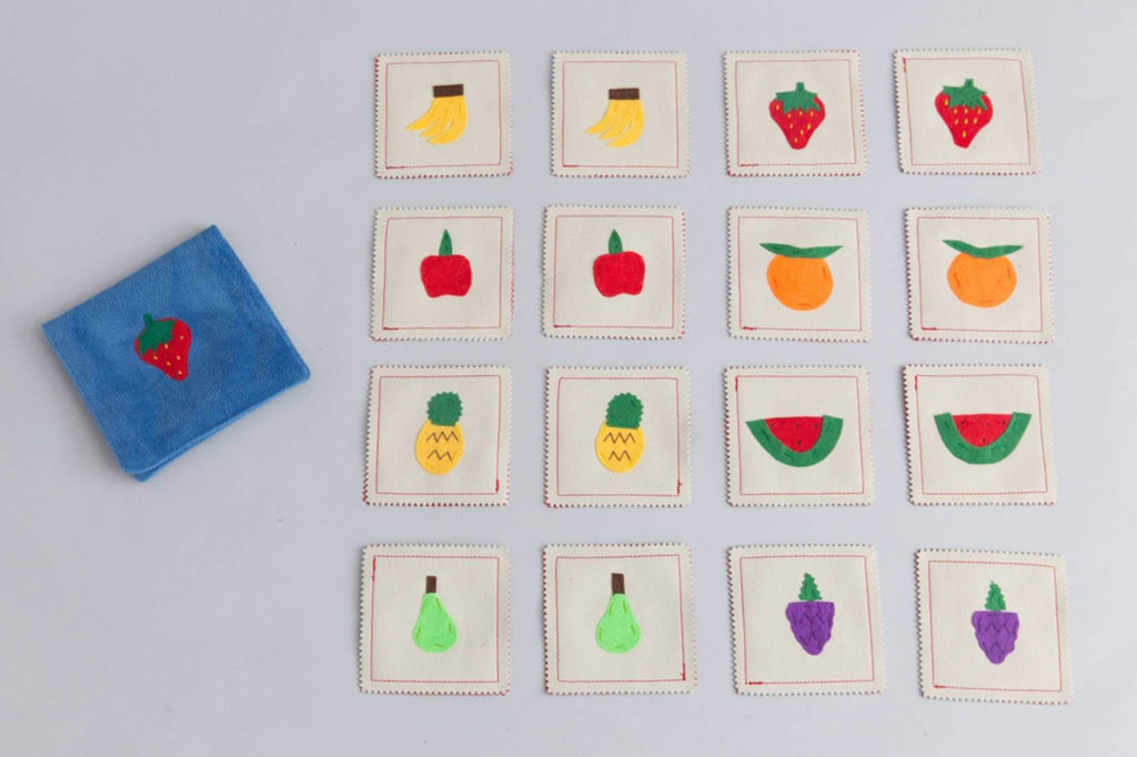 Memory game with fruits painted on the cards on grey surface