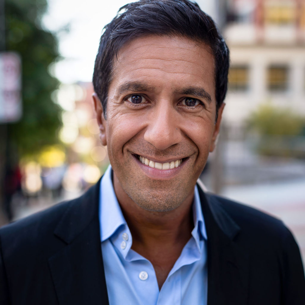 Sanjay Gupta smiling and wearing a blue shirt and black suit