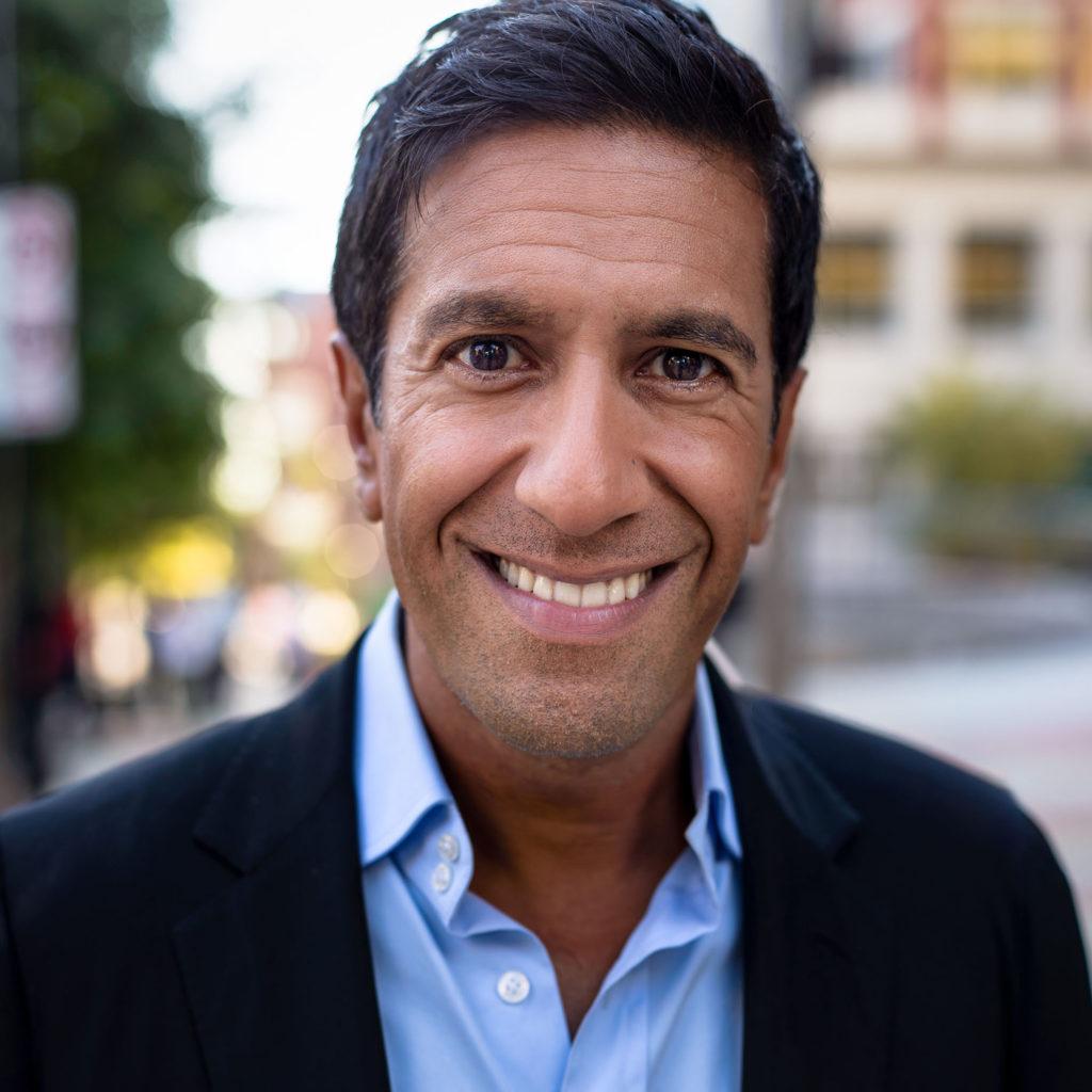 Sanjay Gupta glimlacht en draagt een blauw shirt en zwart pak