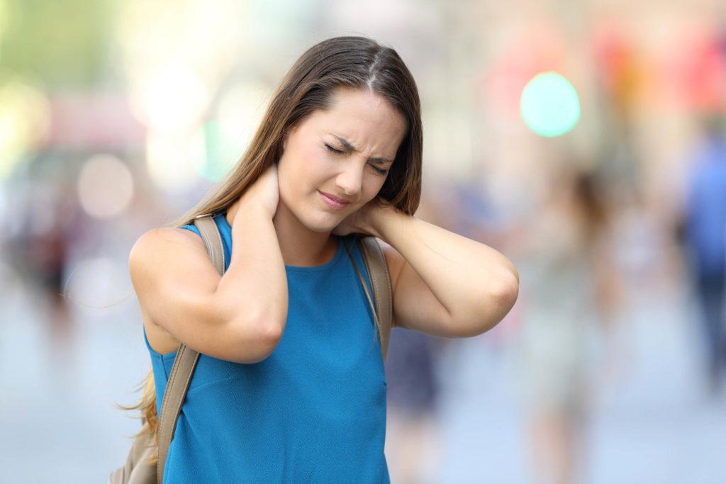 Een vrouw met een uitdrukking van pijn op haar gezicht, die de achterkant van haar nek vasthoudt