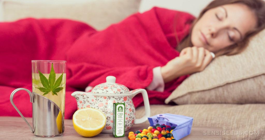 Eine Frau, die auf dem Sofa mit einer Decke liegt. Auf dem Tisch sind verschiedene kalte Behandlungen
